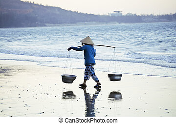 vietnam woman in vietnamese hat walking on seacost at...