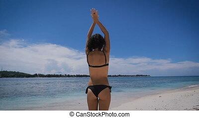 Sexy young girl in black bikini standing on the beach,...