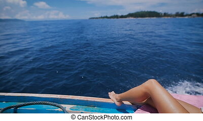 Image of sexy legs of a young woman in marine cruise lying on the deck of sailing boat in open sea. Suntanned bare feet of female traveler crossed on a yacht with ocean and island in the background.