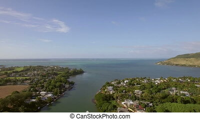 Coastal town and river falling into ocean. Mauritius aerial view