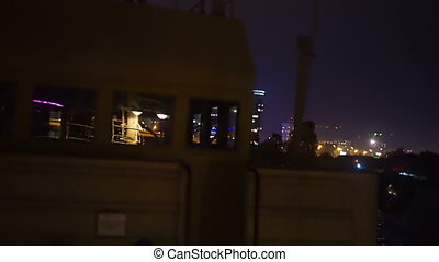 View of the city at night aboard an old boat