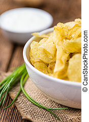 Portion of Potato Chips on wooden background (selective...