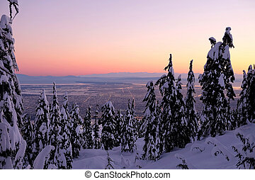City view at sunrise from snowy mountain.