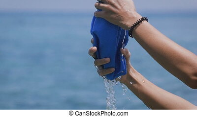 Girl squeezes a blue towel by her hands. The water flows...