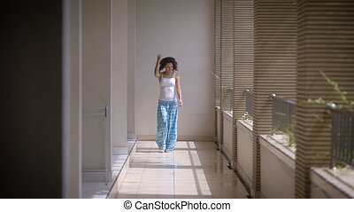 Slender girl walks along a long balcony of a hotel in the resort. At a young brunette wearing a white shirt and blue pants are falling the sun's rays through are not closed windows.