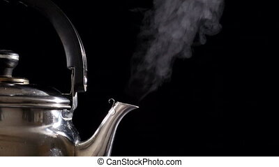 Boiling water in teapot on black background, slow motion -...