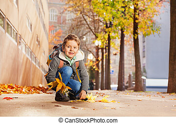 Cute boy collecting maple leaves on his way home - Cute...
