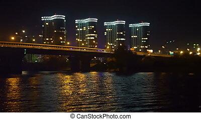 High buildings of housing estate, cars on the night bridge