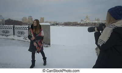 Girl photographing her friend on the street in winter.