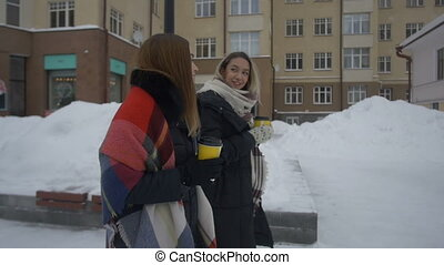 Two friends walking down the street and drink coffee in...