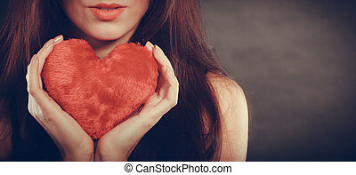 Woman holds red heart love symbol