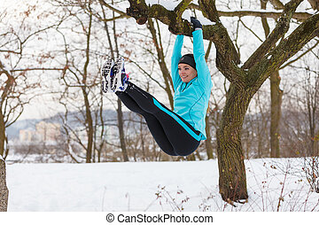 Winter sports, girl exercising on tree. - Girl exercising on...