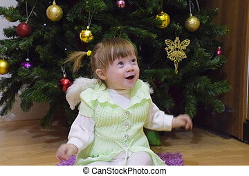 One year old baby girl sitting on the floor near a Christmas...