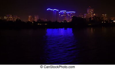 Night city view from the river, housing areas lights