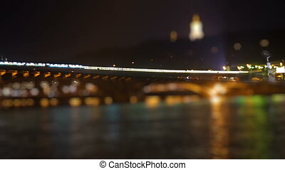 Subway train passes over the luminent river at night