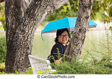 Asia woman holding umbrella in a park