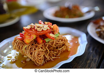 Fried dried sliced squid with sauce and tomato on white...
