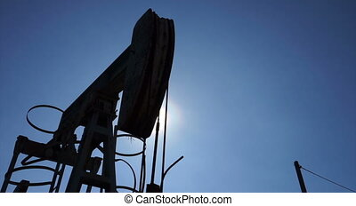 Silhouette of oil pump jacks in operation, gimbal shot