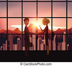 Silhouette business people handshake with city background.