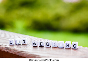 """Word of the cubes """"our wedding"""" on a wooden stand on green..."""