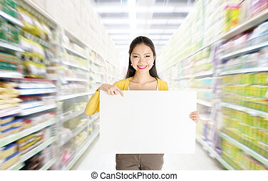 Showing blank card in department store - Young Asian woman...