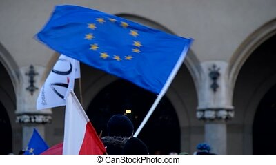 People waving flags of the EU and Poland on demonstration