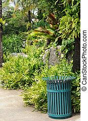 Green steel bin in public garden