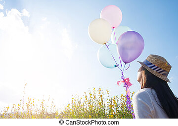 Girl running on the field of yellow flowerwith balloons at...