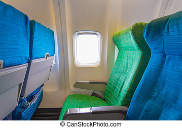 Airplane seat near windows in cabin of huge aircraft.