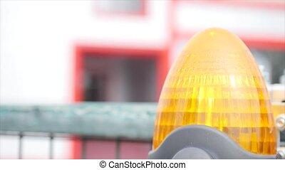 Orange flashing beacon on automatic gate.