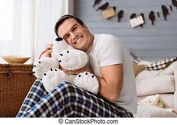 Happy joyful man hugging a stuffed animal - So fluffy and...