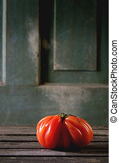 Big red tomato RAF - One big red tomato RAF over old wooden...