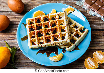 Belgian waffles on blue plate on wooden table with...