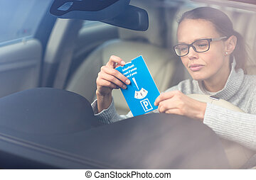 Pretty, young woman driving her elegant new car - putting the necessary parking clock behind the windshield to park legally in a city