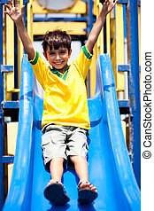 Young smart kid sliding down the swing