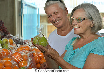 mature couple on food market, choosing fruits
