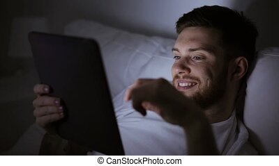 young man with tablet pc in bed at home bedroom -...