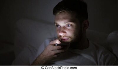 man with smartphone using voice recorder at night -...