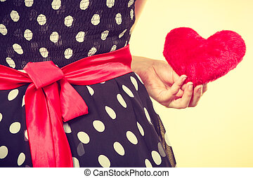 Woman in dotted dress holding red heart - Valentine day...