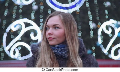 attractive woman at Christmas night smiles looking at the camera in front of park trees decorated sparkling lights