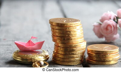 Start up business concept. Stacks of golden coins and a paper boat.