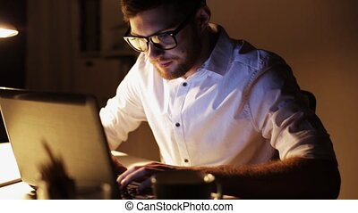 man with laptop and coffee working at night office -...