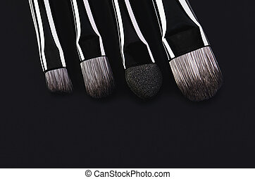 four makeup brushes close-up on a black background. horizontal