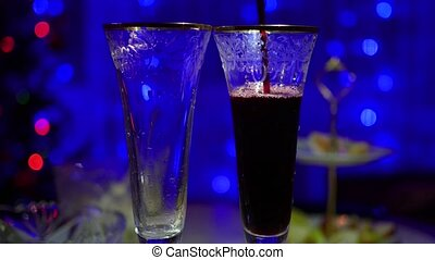 Red wine is poured into glasses. In the background, bokeh lights and garlands of Christmas fir