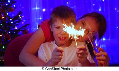 Happy family lit sparklers at the party. In the background, bokeh lights and garlands of Christmas fir