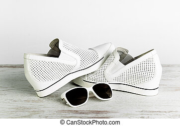 White female shoes and sun glasses on a light background...