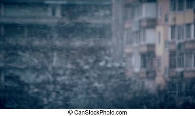 Snow falling on blurred urban background of building - Snow...