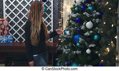 teenage girl's hands is decorating a Christmas tree