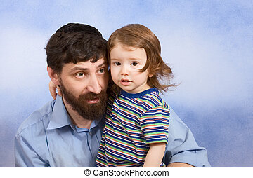 Jewish father in yarmulke hugging with his young son -...