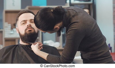 Female barber cuts the beard hair of the male client.
